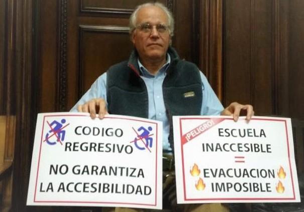 Con carteles en la mano, en uno se lee codigo regresivo no garantiza la accesibilidad, y en el otro: pelibro, escuela inaccesible evacuación imposible